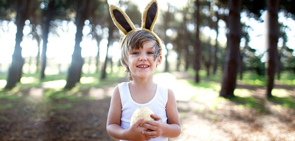 Girl with rabbit ears holding Easter egg