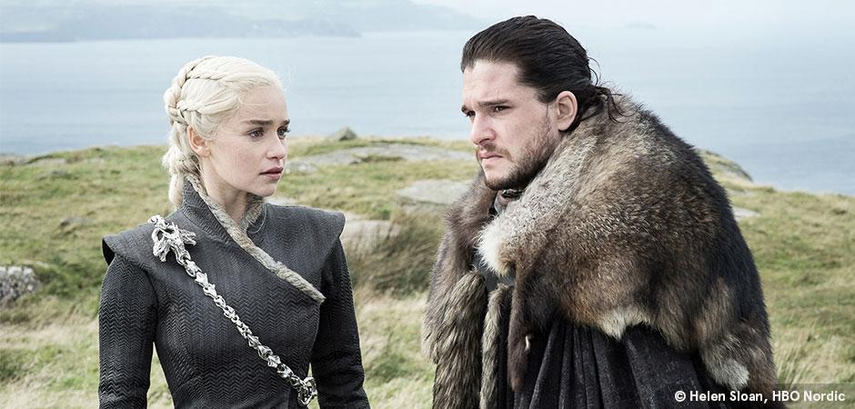 Jon Snow and Daenerys Targaryen stand on a grassy cliff