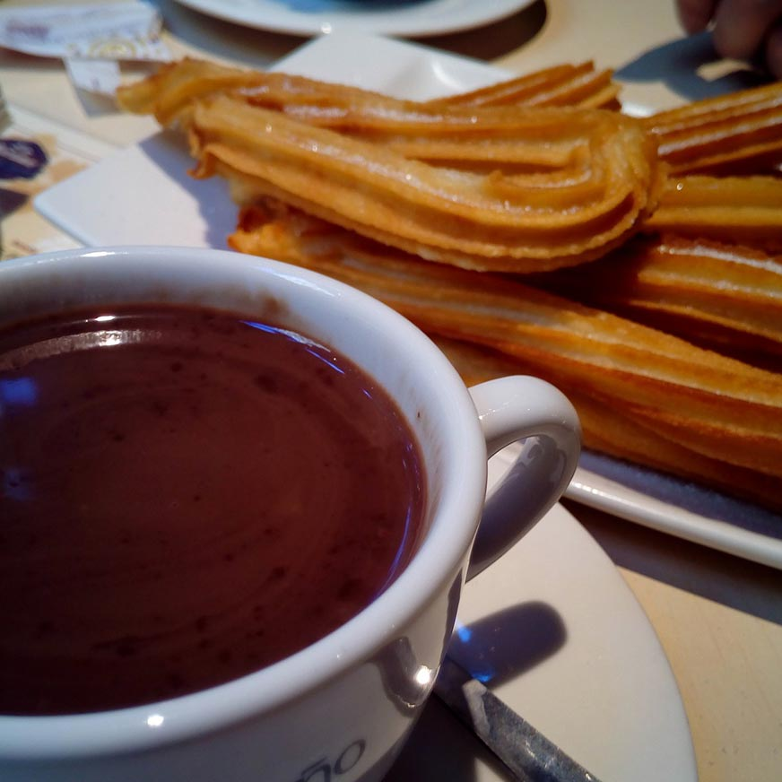 A cup of hot chocolate and a plate of churros next to it