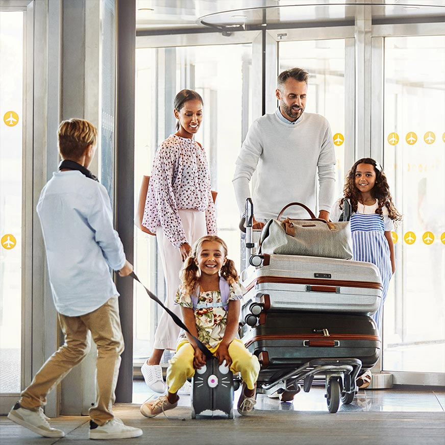 A family with three children passes through the airport, the father pushing a trolley loaded with suitcases, the youngest child sits on a small, rolling suitcase with an animal's face