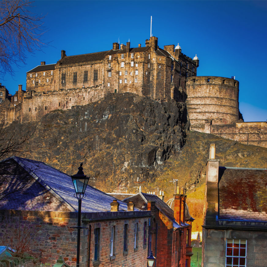 Edinburgh Castle against a blue sky with houses in the foreground