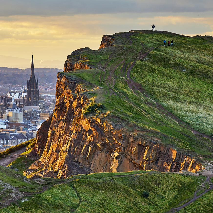 Grass-covered cliffs and the city of Edinburgh in the background