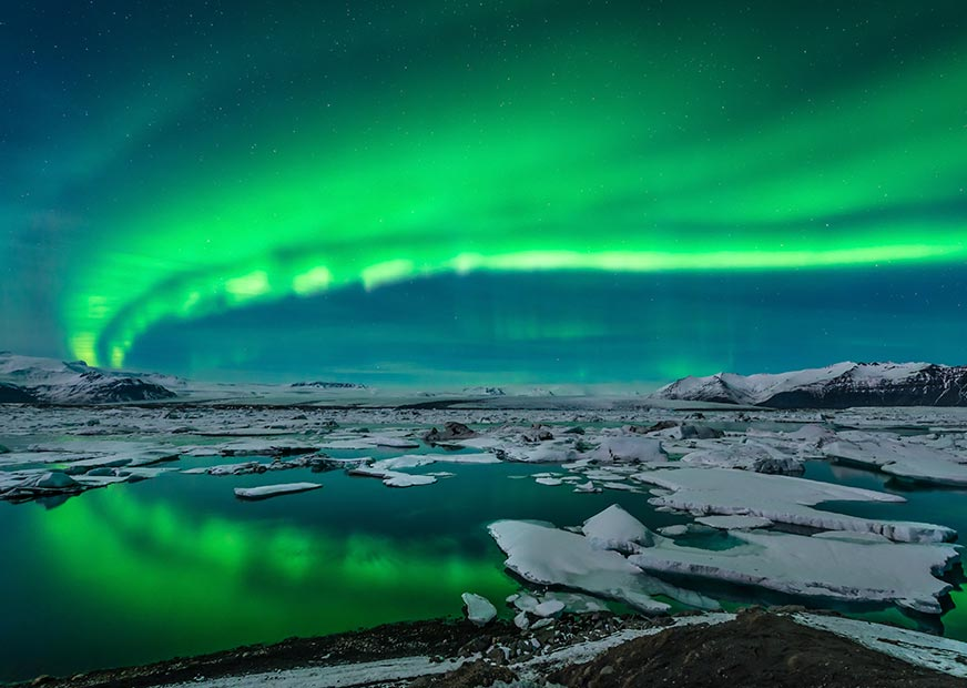 Green Northern Lights over water with ice drifts