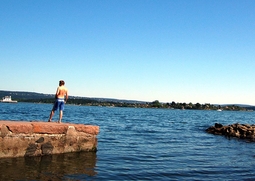 Person standing on the pier at Huk beach near Oslo