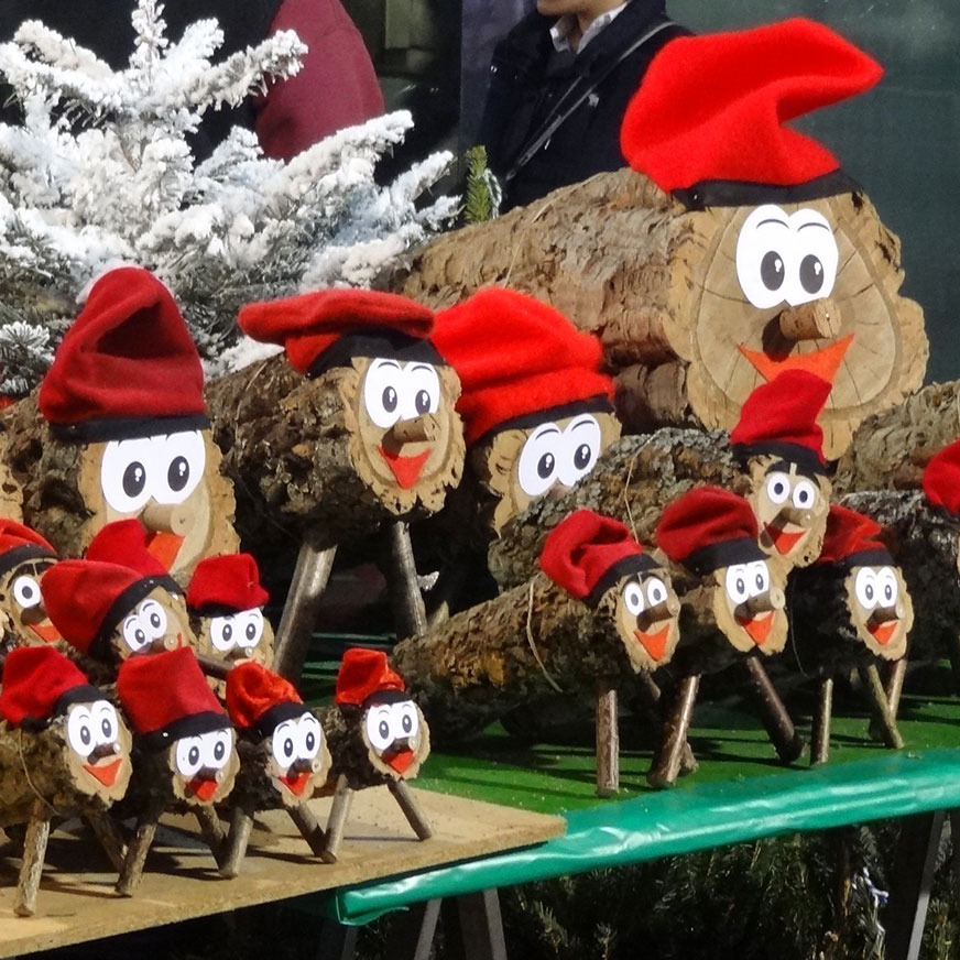 Catalonian Tió de Nadal logs with smiling faces and red hats